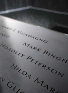 An American flag is seen on inscribed names on the edge of the north pool of the 911 Memorial during memorial observances held at the site of the World Trade Center in New York, September 11, 2014  REUTERS/Chang Lee/Pool (UNITED STATES - Tags: ANNIVERSARY DISASTER TPX IMAGES OF THE DAY) ORG XMIT: NYK318